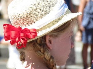 Girl in hat watching parade.